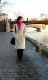 Beautiful girl walking by the Seine embankment poster