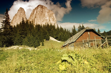 Mountain landscape with an old wooden house