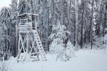 Winter mit viel Schnee im Wald und Jägerstand