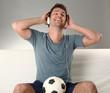 junger mann mit kopfhörern hört musik und hat einen fussball