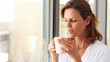 Mature woman blowing cool air in her cup of coffee