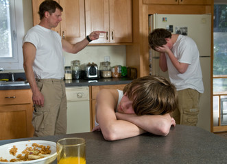 family fight - boy upset as father scolds his brother