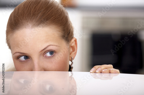 blonde spying over a table