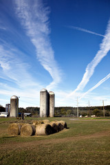 farm with tall silos and blue sky with jet vapor trails