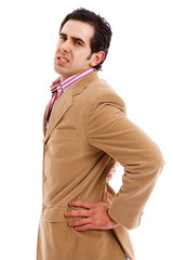 A young business man with a backache, isolated on white