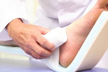 患者の足に包帯を巻く医者の手元