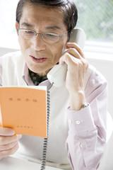 年金手帳を持って電話をしている男性