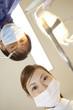 患者を覗き込む男性歯科医と歯科衛生士