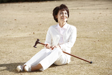 杖を持ちながら座る女性