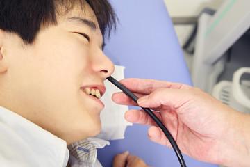 内視鏡を患者の鼻から差し込む医者の手元