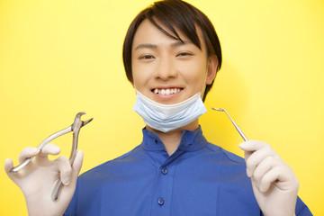 口腔鏡とペンチを持った男性歯科医