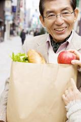 買い物袋を持っている男性