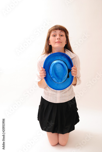 The sad girl with a hat is kneeling