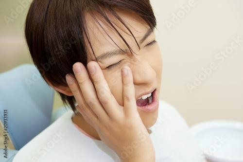 歯痛に顔を歪める男性患者