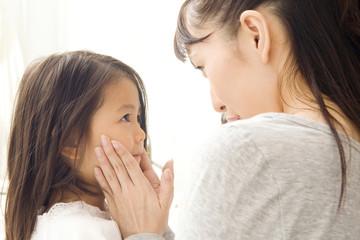 子供のほっぺたに触れる母親