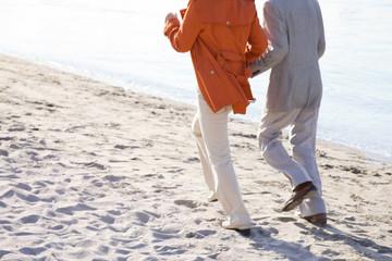 浜辺を走っている夫婦