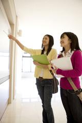 掲示板を見る2人の女子学生