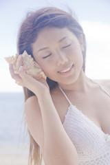 貝に耳を当てる女性