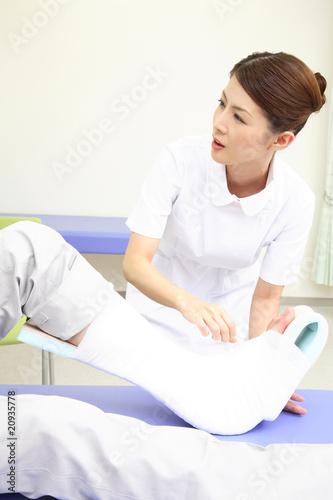 患者の足に包帯を巻く看護師