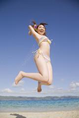 砂浜でジャンプする水着姿の女性