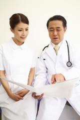 カルテを見ながら会話する医者と看護師
