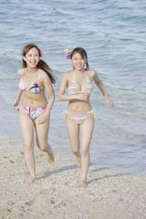 浜辺を駆ける2人の女性