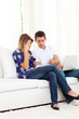 Distressed couple doing their accounts sitting on sofa