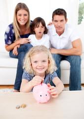 Blond little girl inserting coin in a piggybank