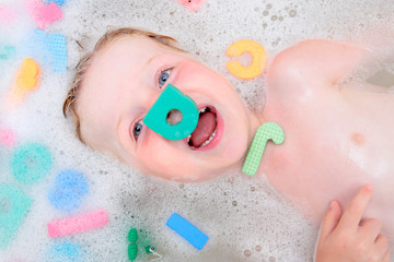 Young boy playing in bubble bath with foam letters
