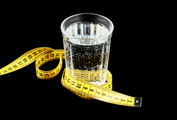 Diet concept, glass of water and measuring tape isolated
