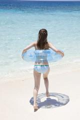 浮き輪を持ち海へと向かう水着女性の後姿