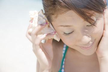 貝殻を耳に当て海の音を聴く水着女性