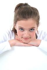 Ein junges Mädchen schaut in die Kamera. Sample Text.
