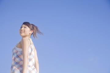 振り返り大空を見上げる女性