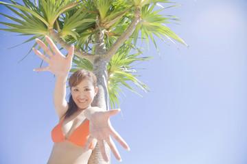 椰子の木の側で手を伸ばす笑顔の水着女性