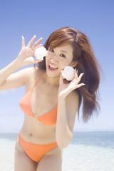 波打ち際で貝がらを持つ笑顔の水着女性