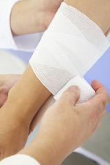 患者の腕を包帯で巻く医者の手元