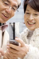 携帯電話の画面を見ている夫婦