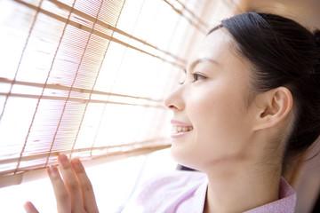 簾越しに外を見る女性