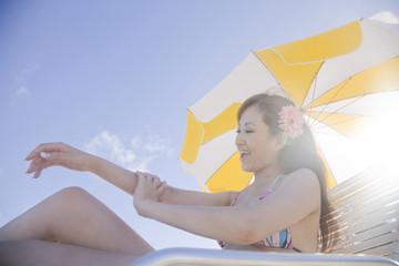 浜辺で日焼止めを身体に塗っている水着姿の女性