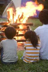 キャンプファイヤーを見る家族の後ろ姿