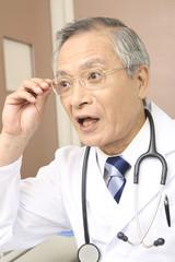 眼鏡に手をかける男性医師