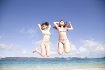 浜辺でジャンプする水着を着た2人の女性
