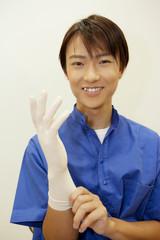 ゴム手袋を付ける歯科医男性