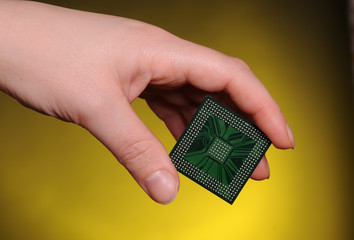 Microelectronics concept. Female hand holdig chip