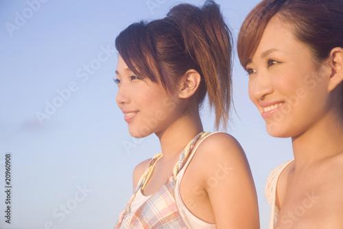 夕暮れに遠くを見つめる女性2人