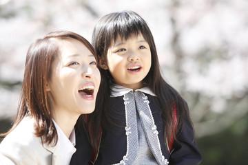 桜の木を見上げる小学生女子と母親