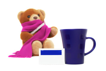 Medicine, a cup and blurred sick Teddy bear isolated on white