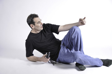 Man laying on studio  floor and pointing