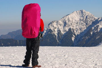 asian mountaineer stand on the snow with mountain scenery.